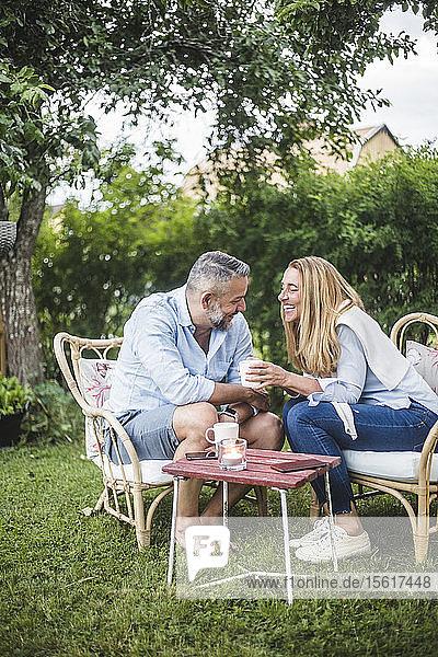 Lächelndes reifes Paar redet im Hinterhof sitzend