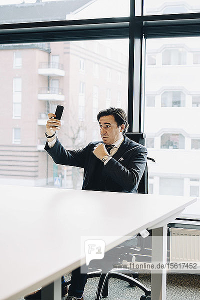 Businessman taking selfie while sitting at desk in office
