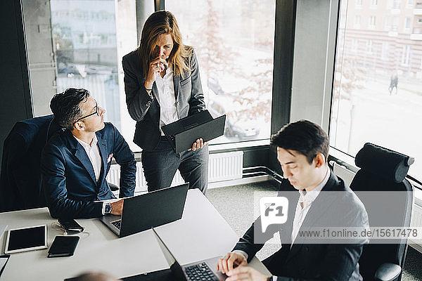 Geschäftsfrau diskutiert mit einem Kollegen über Laptop  während ein Geschäftsmann am Konferenztisch im Büro arbeitet