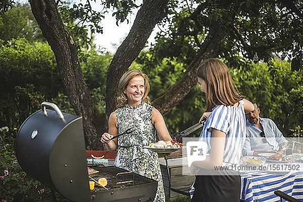 Lächelnde Mutter sieht Tochter an  die bei der Zubereitung von Essen am Grill im Hinterhof während der Wochenendparty hilft