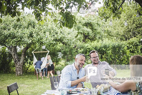 Frau mit Handy fotografiert männliche Freunde beim Trinken auf Gartenparty
