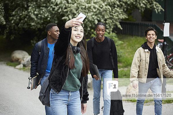 Lächelndes Teenagermädchen  das sich beim Gehen auf der Straße gegen Freunde stellt