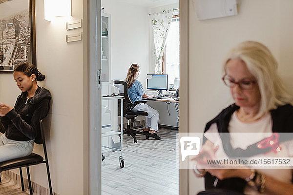 Frauen  die Mobiltelefone benutzen  während sie vor dem medizinischen Untersuchungsraum warten