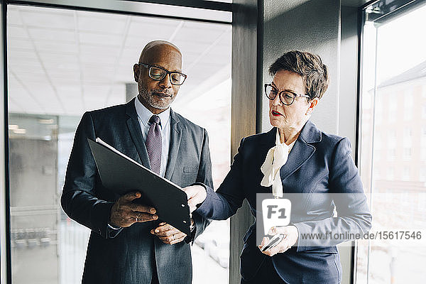 Leitende Geschäftsfrau erklärt ihren Kollegen im Konferenzraum im Büro die Strategie