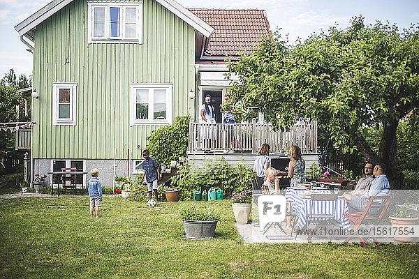 Reife Freunde feiern am Sommerwochenende eine Gartenparty  während Kinder im Garten spielen