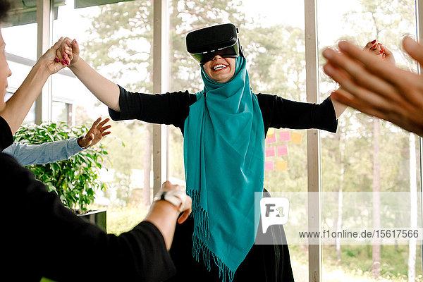 Fröhliche Geschäftsfrau hält die Hand ihres Kollegen  während sie den Virtual-Reality-Simulator während des Kick-off-Meetings bei der Versammlung benutzt