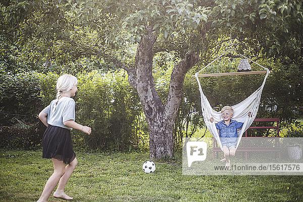 Schwester rennt zum Bruder  der auf der Schaukel im Garten sitzt