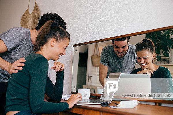 Freund und Freundin lächeln beim Blick auf den Laptop im Schlafzimmer