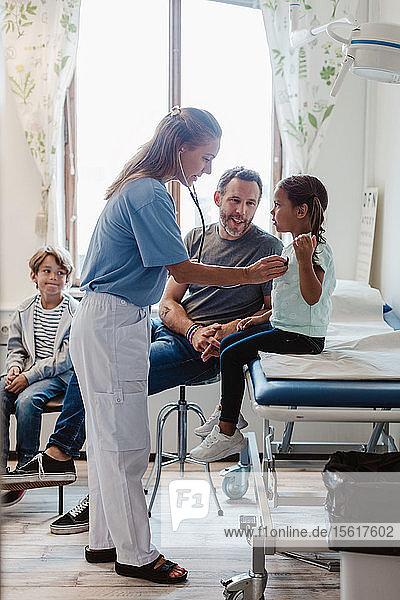 Pädiater untersucht Mädchen mit Stethoskop  während er mit der Familie im Untersuchungsraum sitzt