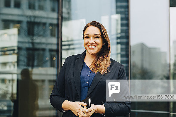 Portrait of smiling businesswoman standing against glass building