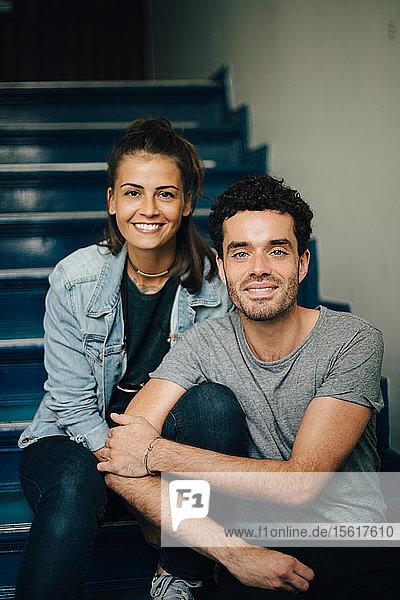 Porträt eines lächelnden Paares  das auf Stufen in einer Wohnung sitzt