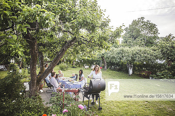 Frau bereitet Essen vor oder grillt  während die Familie im Hinterhof am Tisch sitzt