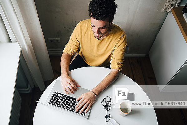 High angle view of mid adult man using laptop at table