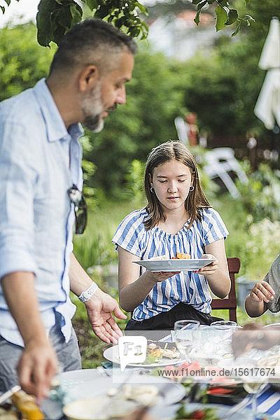 Mädchen hält Speiseteller  während sie mit der Familie im Garten am Tisch sitzt