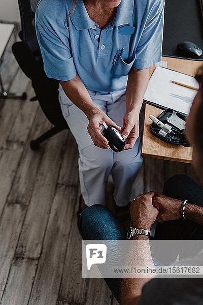 Hochwinkelansicht der Krankenschwester  die das Glaukometer hält  während sie mit dem männlichen Patienten im Krankenhaus sitzt