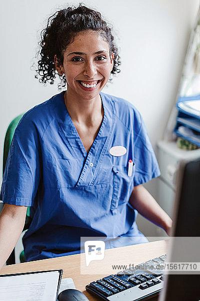 Portrait of smiling female nurse sitting at desk in hospital