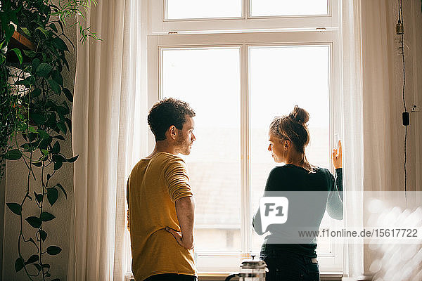 Couple talking while standing by window at home