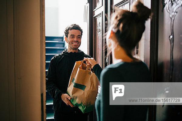 Lächelnder Zusteller übergibt Tasche an am Eingang stehende Frau