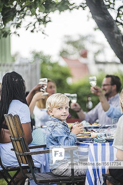 Junge trinkt  während er auf einem Stuhl bei einer Gartenparty mit Freunden und Familie sitzt