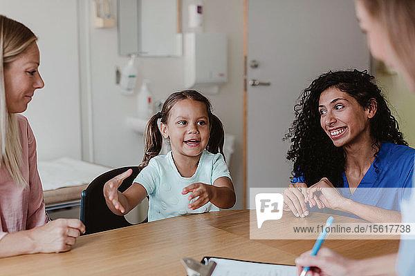 Mädchen spricht mit Arzt  während lächelnde Mutter und Krankenschwester sie im Krankenhaus anschauen