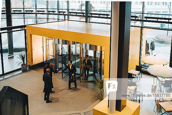 High angle view of business colleagues greeting while entering in office