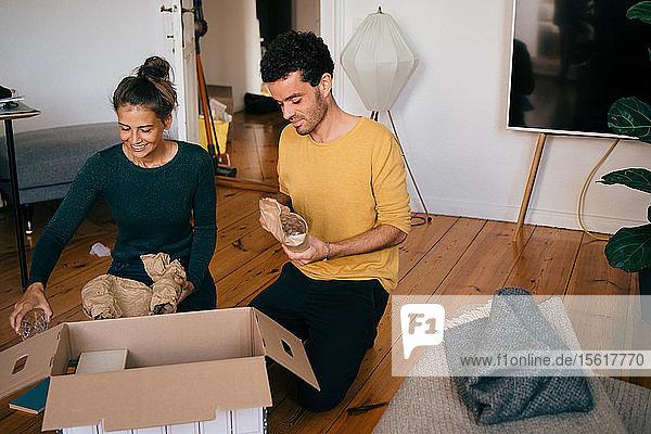 Paar beim Herausnehmen der Gläser aus dem Kasten im Wohnzimmer im neuen Zuhause