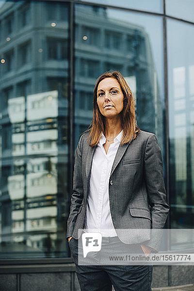 Porträt einer selbstbewussten Geschäftsfrau  die sich gegen die Reflexion über ein Glasgebäude stellt