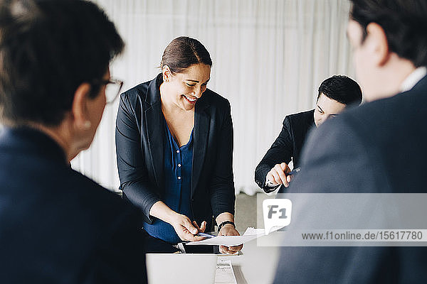 Businesswoman smiling while explaining ideas to colleagues in board room at office