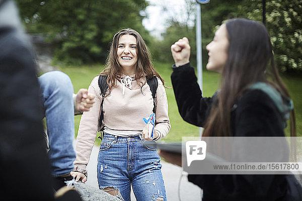 Fröhliche Freundinnen stehen im Park