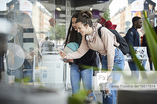 Smiling female friends photographing while standing by store window in city
