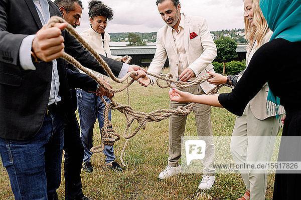 Multi-ethnische männliche und weibliche Kollegen halten Seil  während sie im Rasen stehen