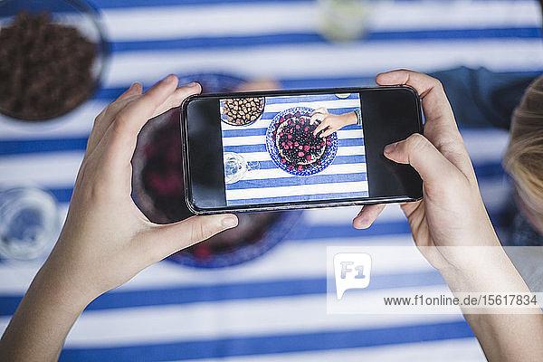 Geschnittene Hand eines Mädchens mit Smartphone fotografiert Jungen beim Dessert am Tisch