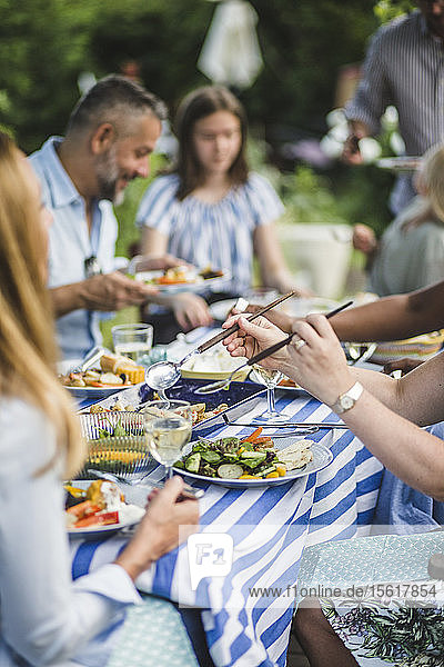 Woman serving food while sitting with friends and family at backyard during weekend party