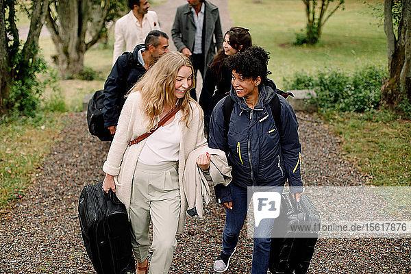 Lächelnde Berufstätige  die sich unterhalten  während sie mit Kollegen auf einem Fußweg während einer Geschäftsreise gehen