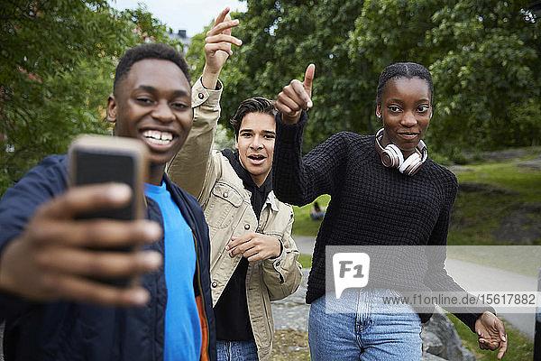 Glückliche Freunde schauen auf Smartphone  während sie im Park Tanz üben