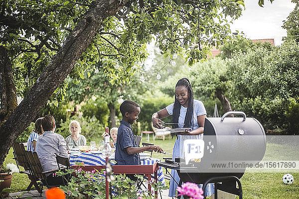 Lächelnde Mutter und Sohn bereiten während der Gartenparty gemeinsam Essen auf dem Grill zu