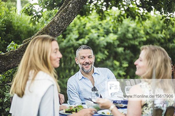 Lächelnder  reifer Mann sieht Freundinnen an  während er am Wochenende eine Gartenparty genießt