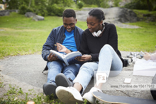 Freundinnen in voller Länge assistieren dem Mann beim Studium im Park