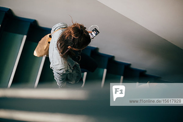High angle view of woman moving down on stairs in apartment