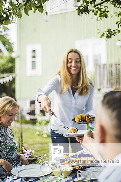 Female serving grilled corns to friends at dining table in backyard party