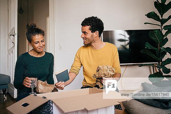 Lächelnder Freund zeigt seiner Freundin einen Roman  während er die Brille aus der Schachtel im Wohnzimmer in seinem neuen Zuhause nimmt