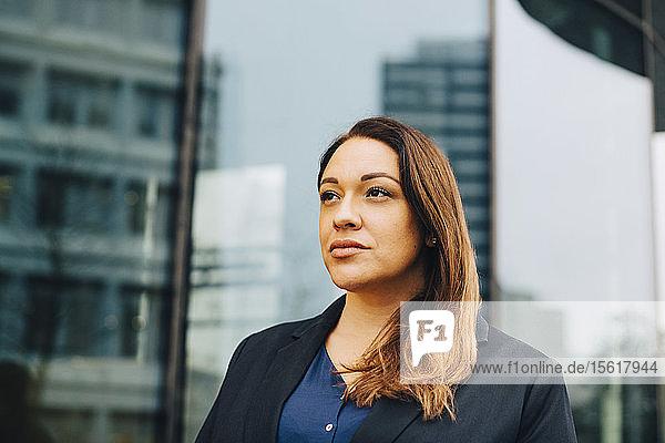 Zuversichtlich nachdenkliche Geschäftsfrau schaut weg gegen das Amt
