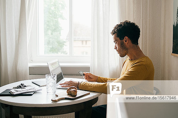 Mid adult man with credit card using laptop while sitting at table in living room