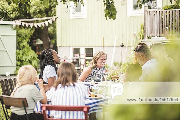 Glückliche Freunde und Familie beim gemeinsamen Essen auf der Gartenparty