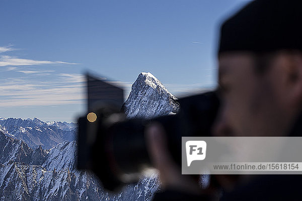 Photographer taking pictures in Mont Blanc range with mountain peak in background  Chamonix-Mont-Blanc  Haute-Savoie  France
