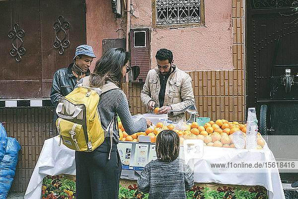 Mother with son buying fresh orange juice in street market in Medina  Marrakesh  Morocco