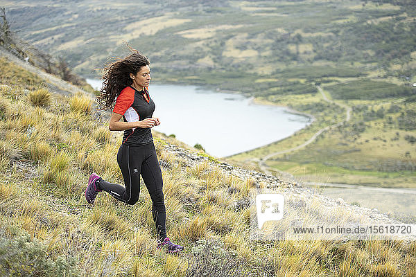 Side view shot of woman trail running in natural setting in Torres del Paine National Park  Magallanes region  Chile