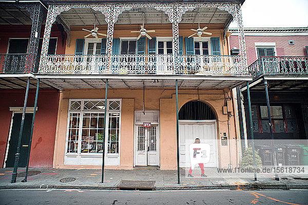 Eine Frau in roter Kleidung geht eine leere Straße in New Orleans  Louisiana  entlang.