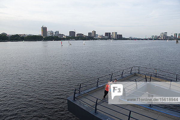 View of two runners on bridge along Charles River  Boston  Massachusetts  USA