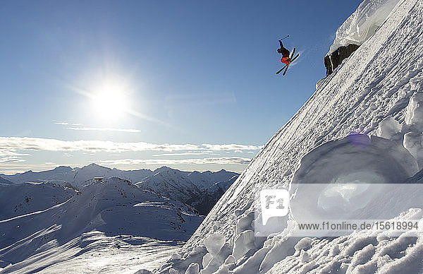 A skier airs off of a cornice and is above the mountains in the background.